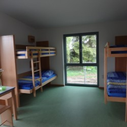 Ein Vierbettzimmer mit Etagenbetten im Freizeitheim Krekel für Gruppenreisen in Deutschland.