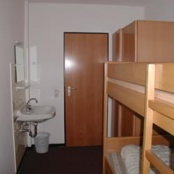 Mehrbettzimmer mit Etagenbett, Kleiderschrank und Waschbecken im Gruppenheim Jugendhaus Monschau in Deutschland.