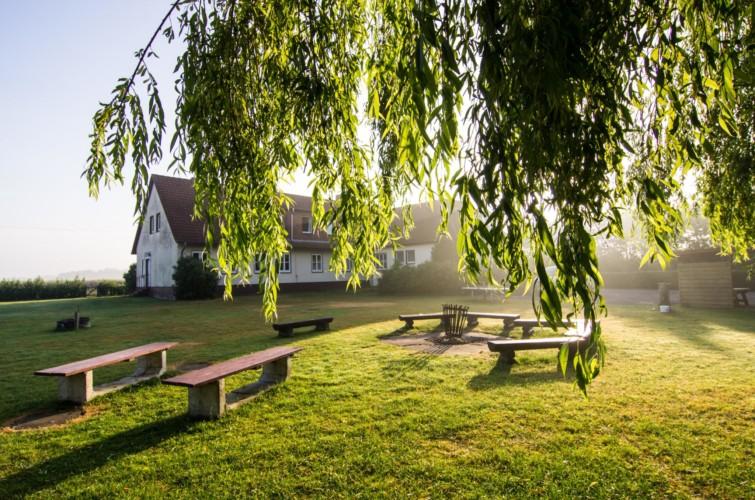 Lagerfeuerstelle und Sitzbänke im Garten am Gruppenhaus Freizeitheim Settrup für Kinder und Jugendreisen in Deutschland.