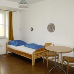 Ein Schlafzimmer mit Holzbetten, Sitzgruppe und Kleiderschrank im niedersächsischen Freizeitheim Settrup für Kinder und Jugendfreizeiten in Deutschland.