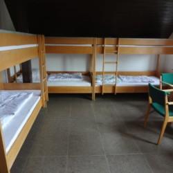 Ein Schlafzimmer mit Etagenbetten und Sitzgruppe im Gruppenheim Freizeitheim Settrup für Kinder und Jugendfreizeiten in Deutschland.