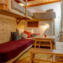 Ein Schlafzimmer mit Hochbetten und Sitzgruppe im Gruppenhaus Strandlodges Panorama in Griechenland.