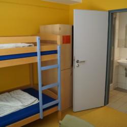 DEHE Ein Schlafzimmer mit eigenem Bad im Freizeithaus Heliand für Kinder und Jugendfreizeiten in Deutschland.