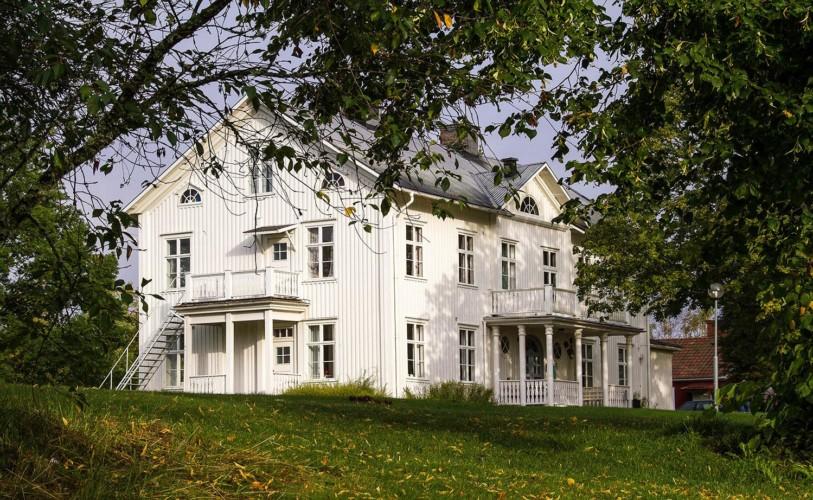 Das schwedische Freizeithaus Berga Gård liegt auf einem grünen Hügel.