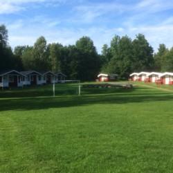 Blockhütten, Fußballplatz, Spielwiese und Lagerfeuer am Gruppenhaus Flahult Ungdomsgård in Schweden.