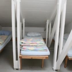 Ein Mehrbettzimmer im Ferienhaus für Gruppen Greagarden in Schweden.