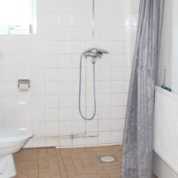 Sanitäre Anlagen mit Dusche, WC und Fenster im Gruppenhaus Tygegården in Schweden.
