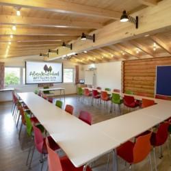 Ein Gruppenraum mit Sitzgruppe und Leinwand im Gruppenhaus Fuchsbau in Deutschland.