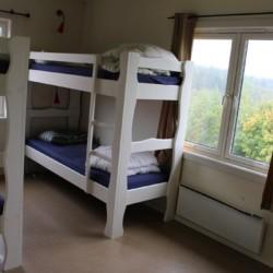 Das Schlafzimmer im norwegischen Freizeitheim Haraset hat einen Ausblick auf dem Wald