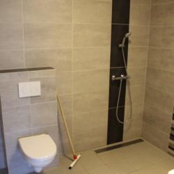 Ein Badezimmer mit Dusche und Toilette im Gruppenhaus Kievitsnest in den Niederlanden.